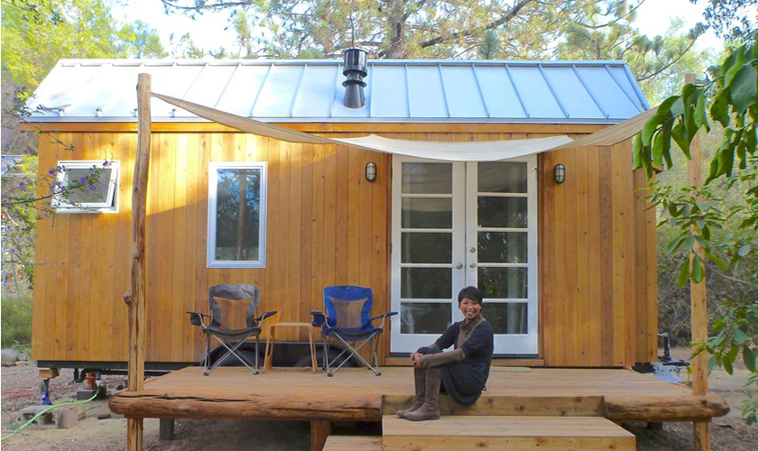 Vina vor ihrem Tiny House - einem winzigen Holzhäuschen auf einem Trailer im Sonnenschein